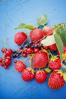 Suculentas frutas maduras de morango, cereja de pássaro e groselha em um fundo enferrujado. estilo sertanejo.
