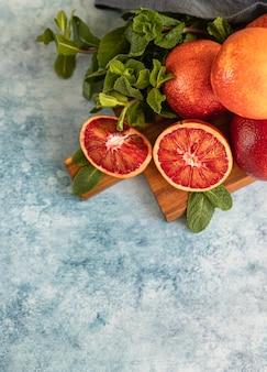 Suculentas laranjas sanguíneas sicilianas fatiadas e inteiras maduras em uma tábua de madeira com hortelã