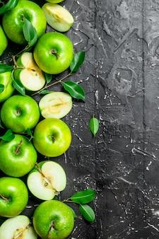 Suculentas maçãs verdes com folhas e fatias de maçãs. em uma superfície rústica escura.
