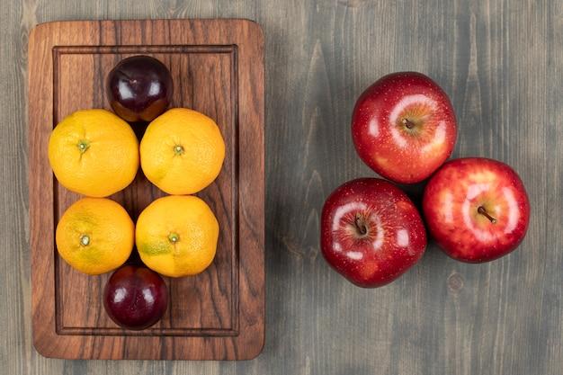Suculentas maçãs vermelhas com ameixas e tangerinas em uma tábua de madeira. foto de alta qualidade