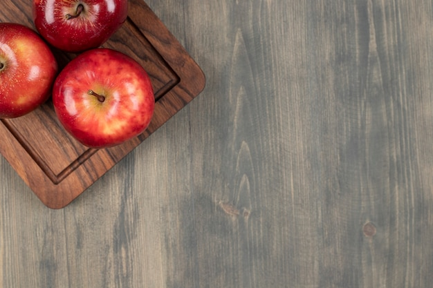 Suculentas maçãs vermelhas em uma tábua de madeira. foto de alta qualidade