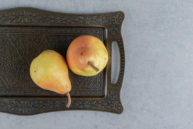 Suculentas peras em uma bandeja ornamentada em mármore