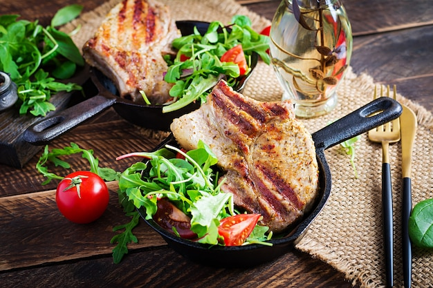 Suculento bife de porco grelhado com ervas com osso na superfície de madeira