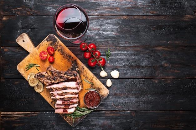 Suculento e saboroso pedaço de carne grelhada, bife de porco, uma taça de vinho tinto e vegetais na mesa. lugar para texto.