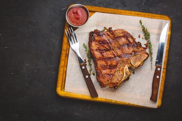 Suculento grelhado grande bife t-bone guarnecido com ervas e sal