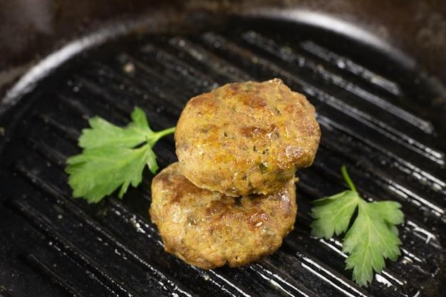 Suculento hambúrguer de carne caseiro costeleta de carne, porco, frango, peru na frigideira de ferro fundido preto com ervas conceito de dieta cetogênica, carnívora e com baixo teor de carboidratos. fechar-se. foco seletivo. copie o espaço