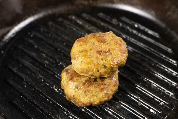 Suculento hambúrguer de carne caseiro costeleta de carne, porco, frango, peru na mesa de frigideira de ferro fundido preto. conceito de dieta cetogênica, carnívora e com baixo teor de carboidratos. fechar-se. foco seletivo. copie o espaço