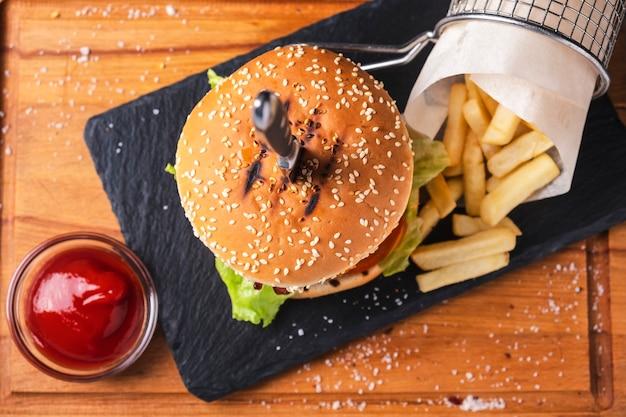 Suculento hambúrguer de carne com batatas fritas e ketchup na placa de madeira. vista do topo. comida rápida