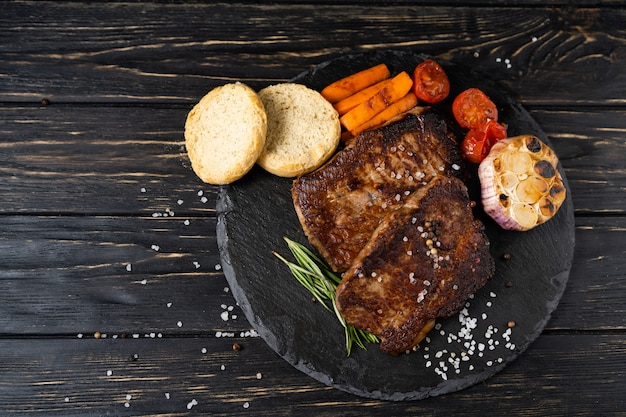 Suculento pedaço de carne frita encontra-se em um prato de pedra contra uma mesa de madeira preta