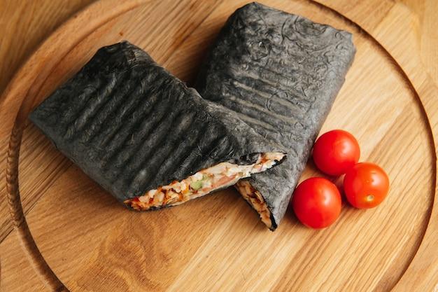 Suculento shawarma preto grelhado em uma placa de madeira com carne de legumes e especiarias. doner kebab preto