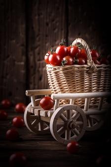 Suculento tomate vermelho na cesta na mesa de madeira