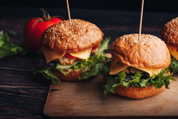 Suculentos hambúrgueres caseiros com carne, queijo, alface, tomate em uma placa