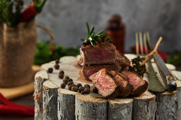 Suculentos pedaços médios de bife de costela em uma panela em uma placa de madeira com um garfo e faca