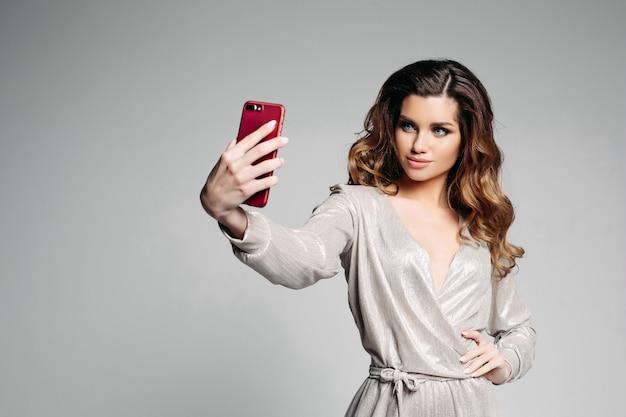 Sudactive modelo feminino em prata vestido tirando foto no smartphone.
