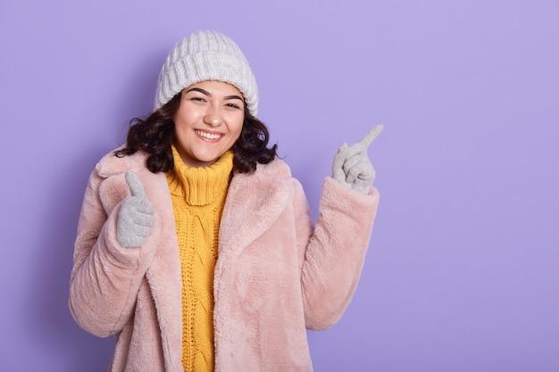 Suéter amarelo sorridente jovem morena, casaco de pele rosa, boné cinza e luvas