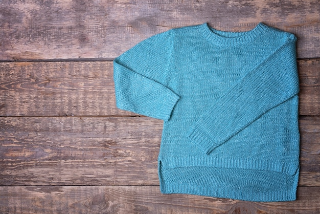 Suéter azul quente em superfície de madeira