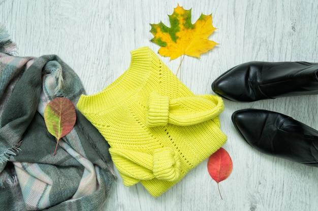 Suéter brilhante, lenço, botas pretas e folhas de outono. conceito de moda