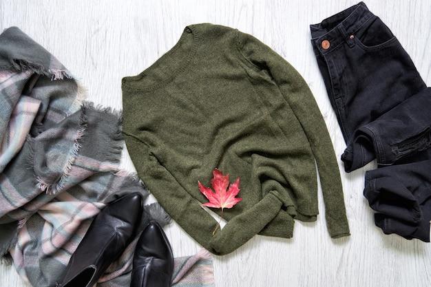 Suéter cáqui, jeans preto e um lenço