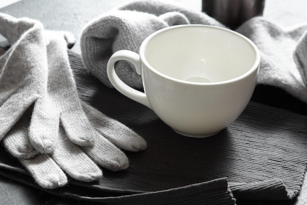 Suéter cinza de malha aconchegante com uma xícara de café em uma mesa de madeira preta
