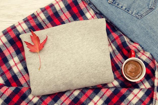 Suéter cinza, jeans, caneca xadrez e café. folhas de outono elegante