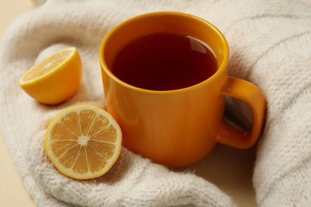 Suéter com xícara de chá e limões em fundo bege