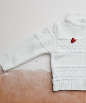 Suéter de lã branco de vista superior com um coração vermelho. postura plana