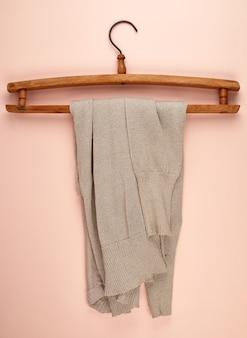 Suéter feminino bege, pendurado em um cabide de madeira vintage
