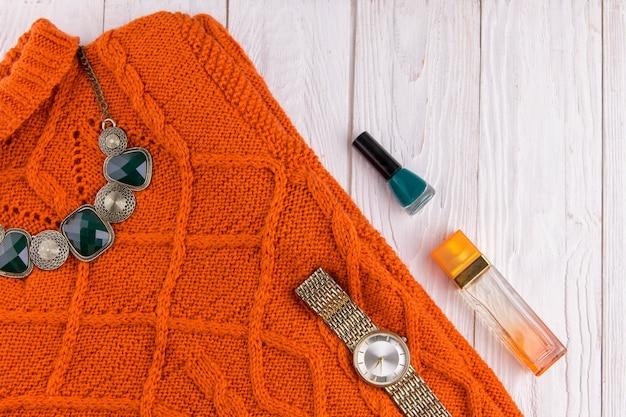Suéter laranja com acessórios e cosméticos. roupa feminina em fundo de madeira