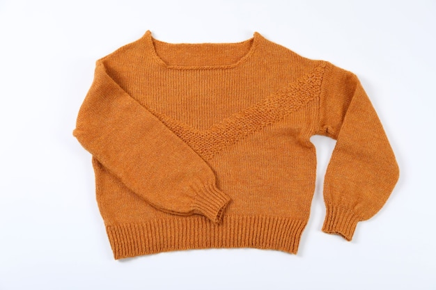 Suéter laranja em fundo branco, vista superior.