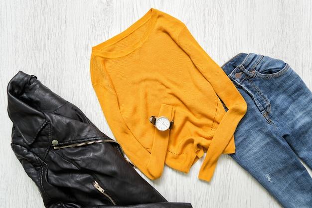 Suéter laranja, relógio, jaqueta preta e calça jeans