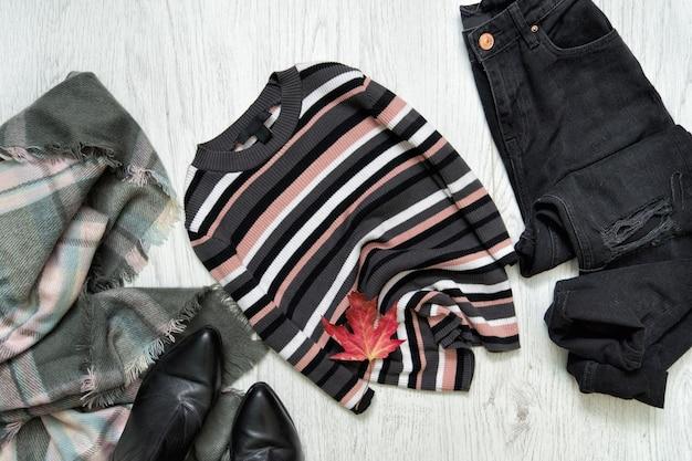 Suéter listrado, jeans preto e lenço na superfície de madeira