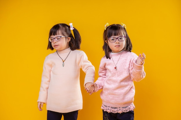 Suéter quente e macio. duas irmãzinhas juntas, de mãos dadas e usando óculos transparentes para visão deficiente
