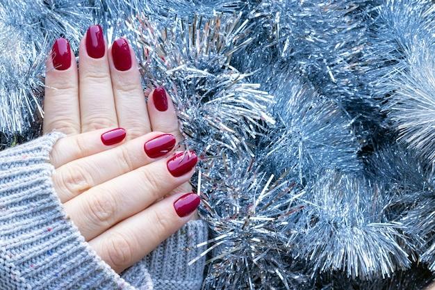 Suéter tricotado com as mãos e unhas bordô em fundo de guirlanda de enfeites de natal prata