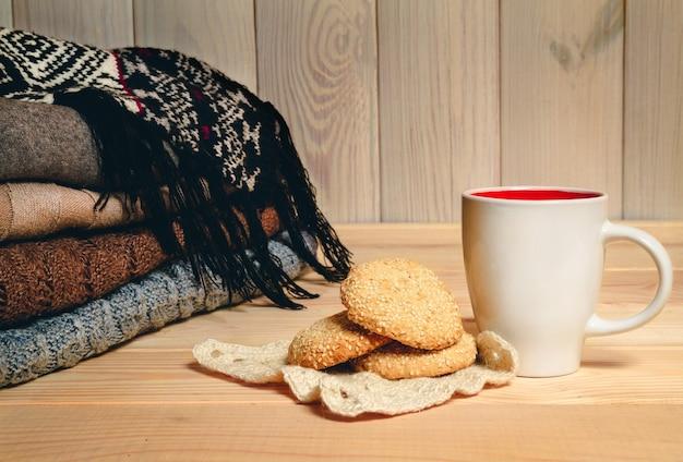 Suéter tricotado, xícara e biscoitos