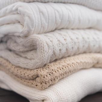 Suéteres brancos e bege estão empilhados diferentes padrões de tricô close-up fundo de outono