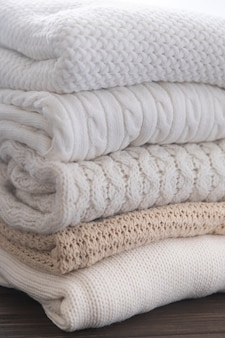 Suéteres brancos e bege são empilhados. diferentes padrões de malha. fundo de outono ou inverno.