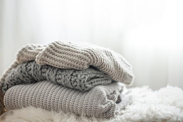 Suéteres de malha cinza aconchegantes empilhados no fundo desfocado, copie o espaço.