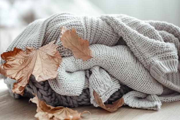 Suéteres de malha em tons pastel e folhas secas de outono em um fundo desfocado.