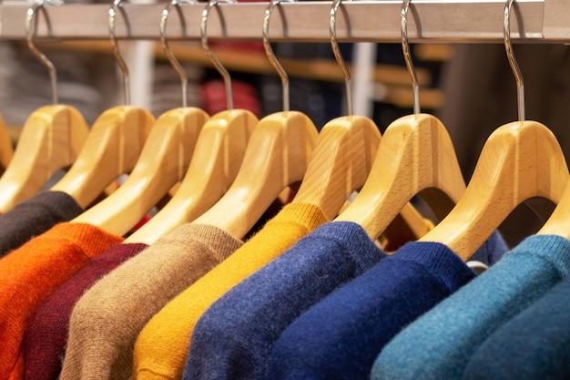 Suéteres de malha multicoloridos pendurados em cabides de madeira, roupas modernas de outono