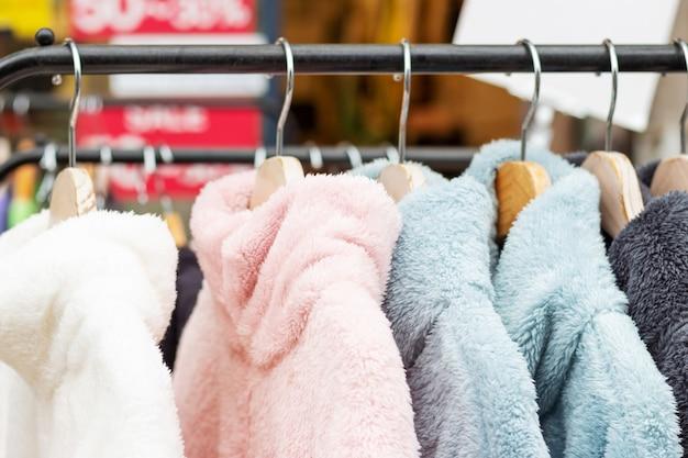 Suéteres de pelúcia em cabides de madeira em close-up da loja.