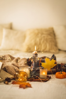 Suéteres e velas com decoração de outono e livro para ler detalhes de natureza morta no interior da casa