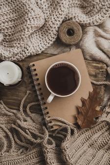 Suéteres e xícara de chá com caderno, vela e tricô