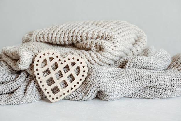 Suéteres quentes de malha em tons pastel e um coração de madeira decorativo.