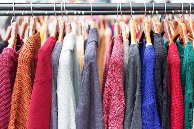 Suéteres quentes em cabides de madeira em close-up da loja.