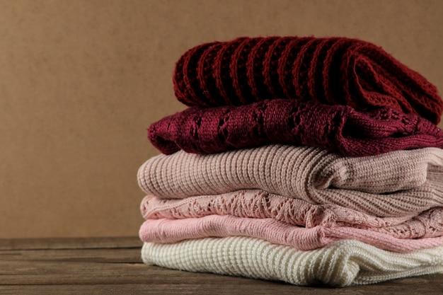 Suéteres quentes empilhados em um fundo de madeira marrom