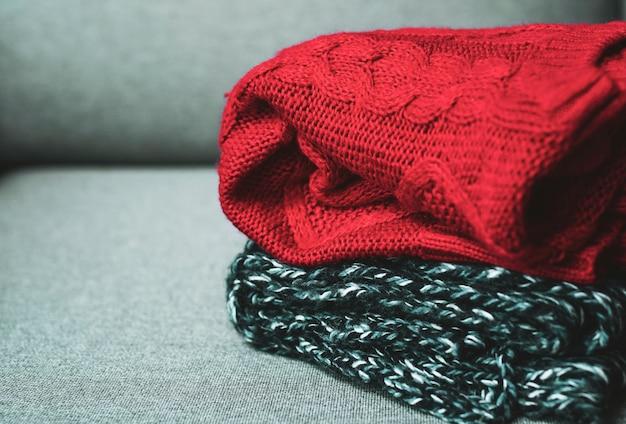 Suéteres quentes no sofá cinza