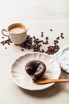 Suflê de bolo de chocolate quente no prato com café e grãos de café torrados