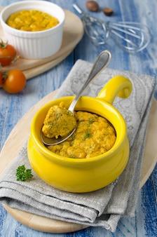Suflê de queijo assado francês com cenoura e endro em ramekin branco