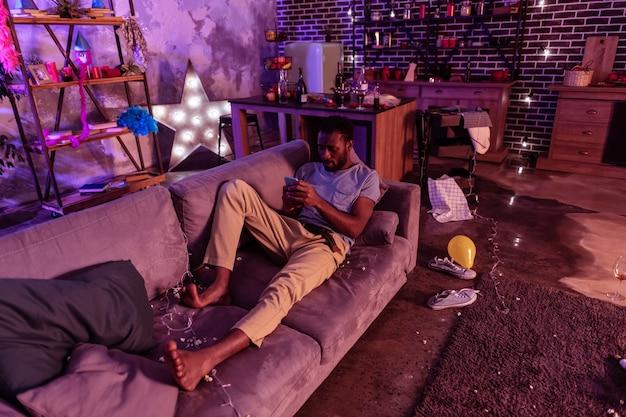 Sujeira e bagunça. cara descuidado de pele escura se divertindo com o smartphone enquanto fica deitado entre sobras e coletas