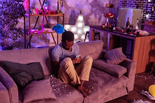 Sujeira e sobras. homem afro-americano de cabelo curto sentado com as pernas cruzadas e observando informações no smartphone
